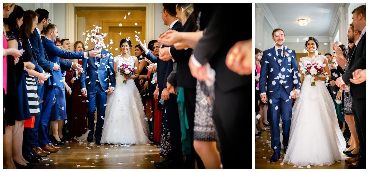 Die Gäste haben einen Spalier gebildet und bewerfen das Brautpaar mit Blütenblättern