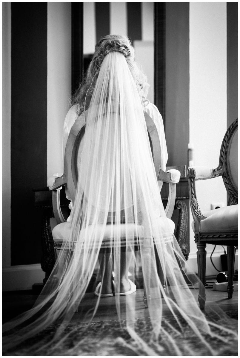 Die Braut sitzt auf einem Stuhl vor dem Spiegel beim Getting Ready auf Schloss Hertefeld in Weeze