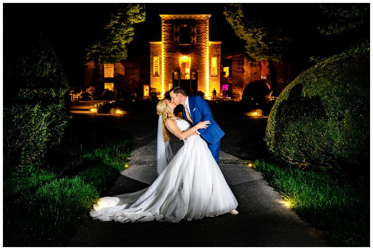 Das Brautpaar küsst sich nachts vor der Hochzeitslocation Schloss Hertefeld in Weeze.