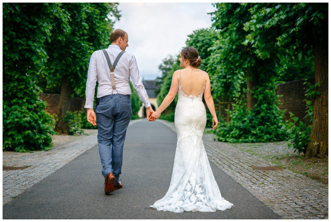 Hochzeitsshooting in Dormagen, das Brautpaar läuft Hand in Hand einen Weg entlang.