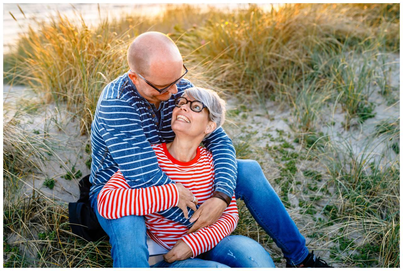 Engagementshooting am Strand von Sylt, das Brautpaar sitzt in den Dünen und strahlt sich an