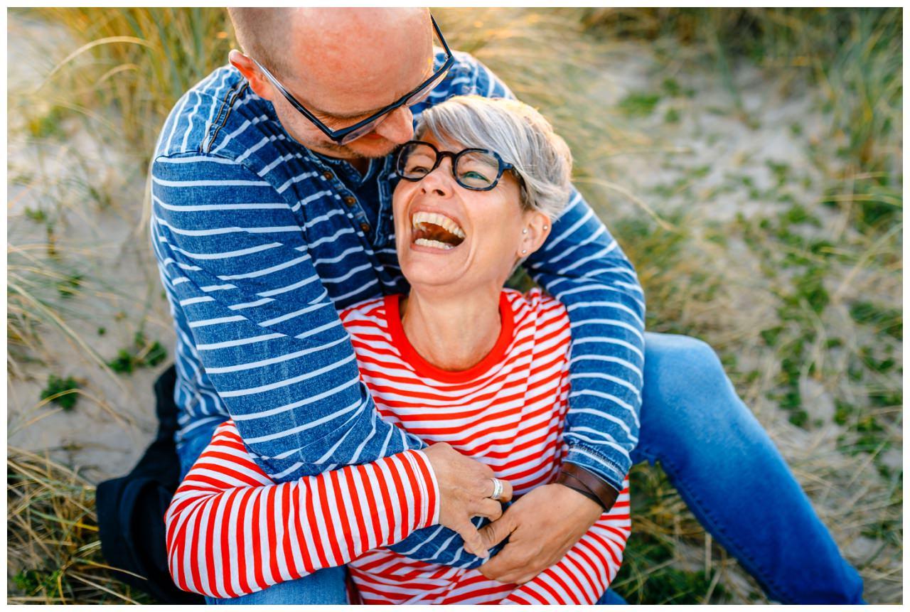 Paarshooting am Strand von Sylt - das verliebte Paar lacht herzlich