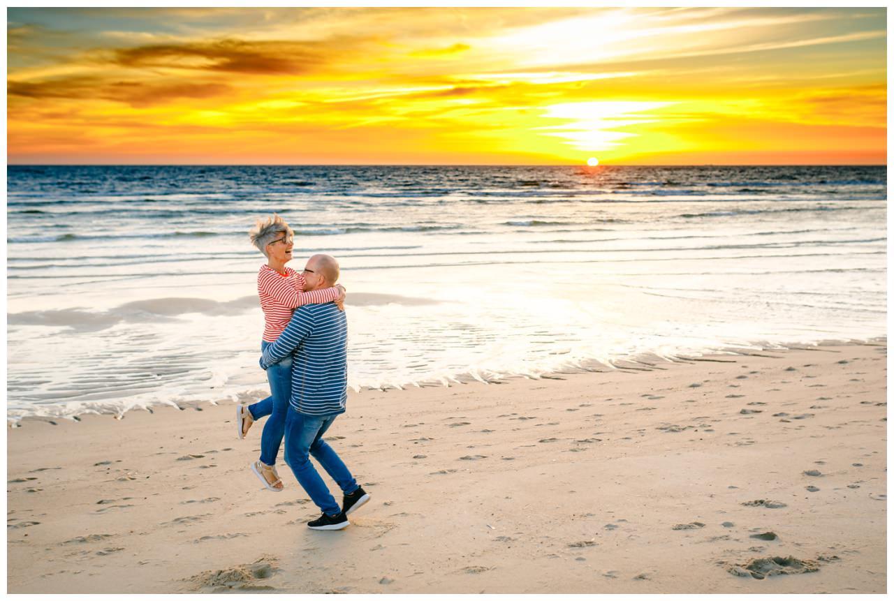 Hochzeit auf Sylt, der Mann hebt die Frau hoch und dreht sie im Kreis am Strand