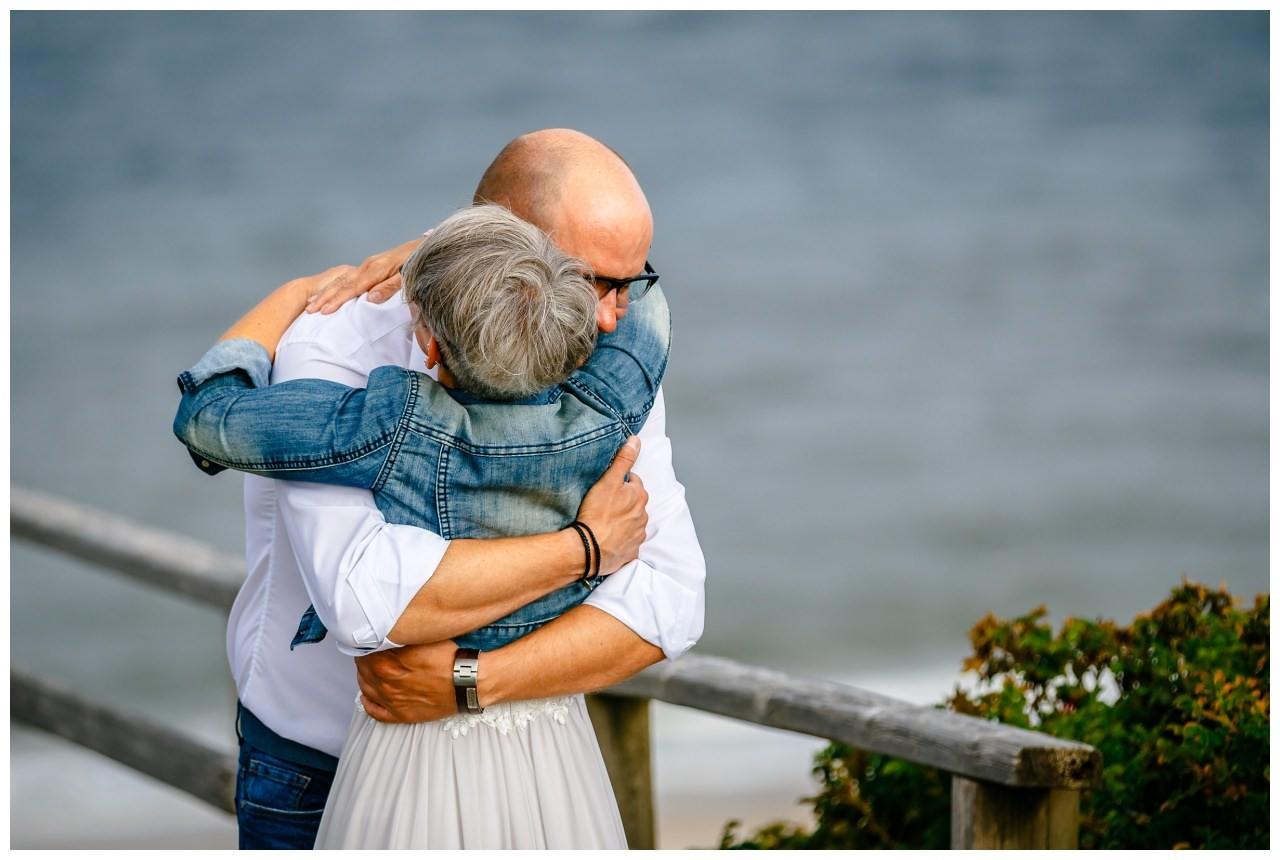 Das Brautpaar umarmt sich am Strand von Sylt.