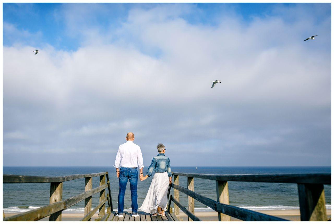 Das Brautpaar läuft zum Strand von Sylt, Möwen fliegen über ihren Köpfen