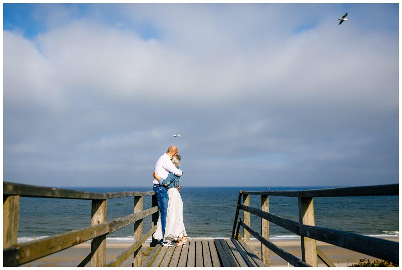 Das Brautpaar kuschelt vor der Hochzeit auf Sylt auf einer Düne.