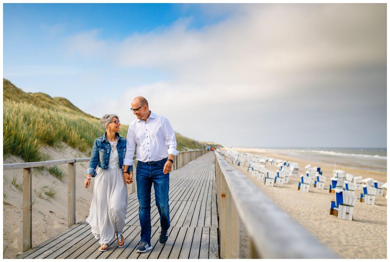 Am Hochzeitsmorgen gehen Braut und Bräutigam am Strand von Sylt spazieren.