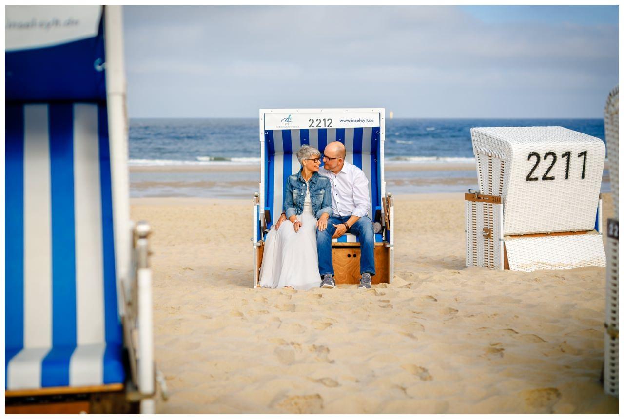 Braut und Bräutigam sitzen im Strandkorb am Strand auf Sylt.