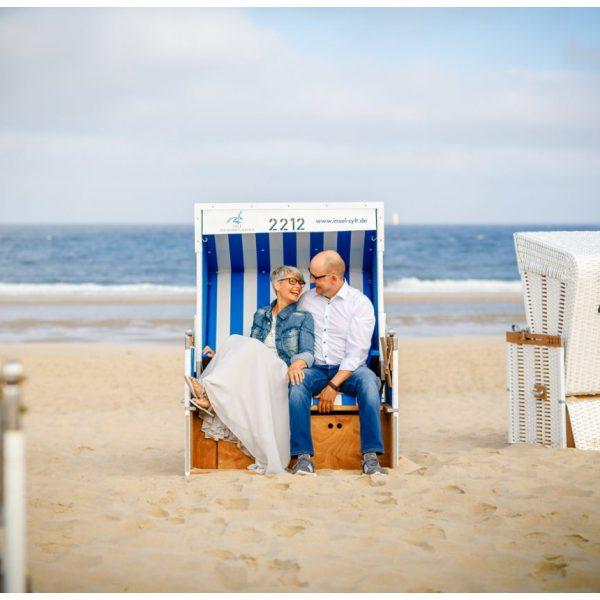 Hochzeit auf Sylt, das Brautpaar kuschelt im Strandkorb.