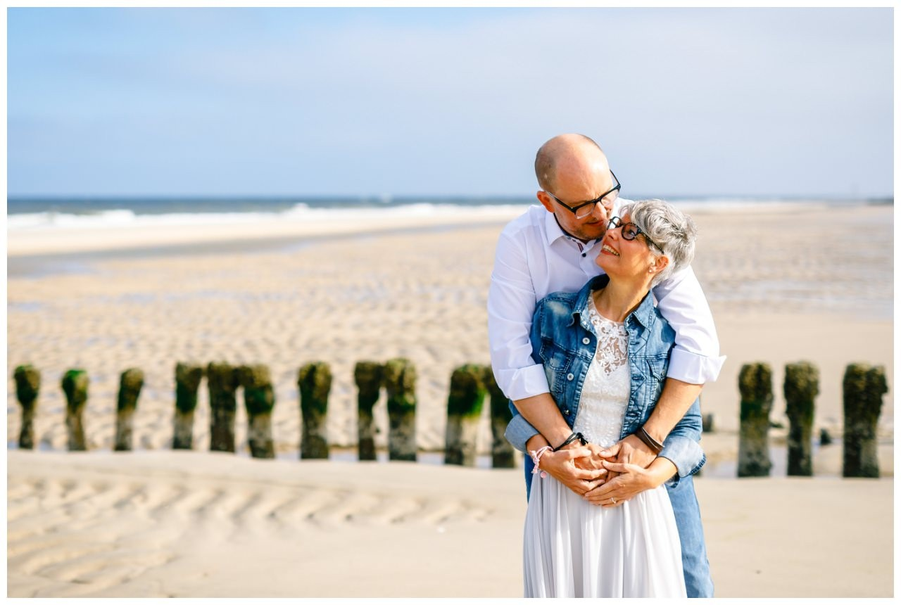 Standesamtliche Trauung auf Sylt, das Brautpaar kuschelt am Strand.