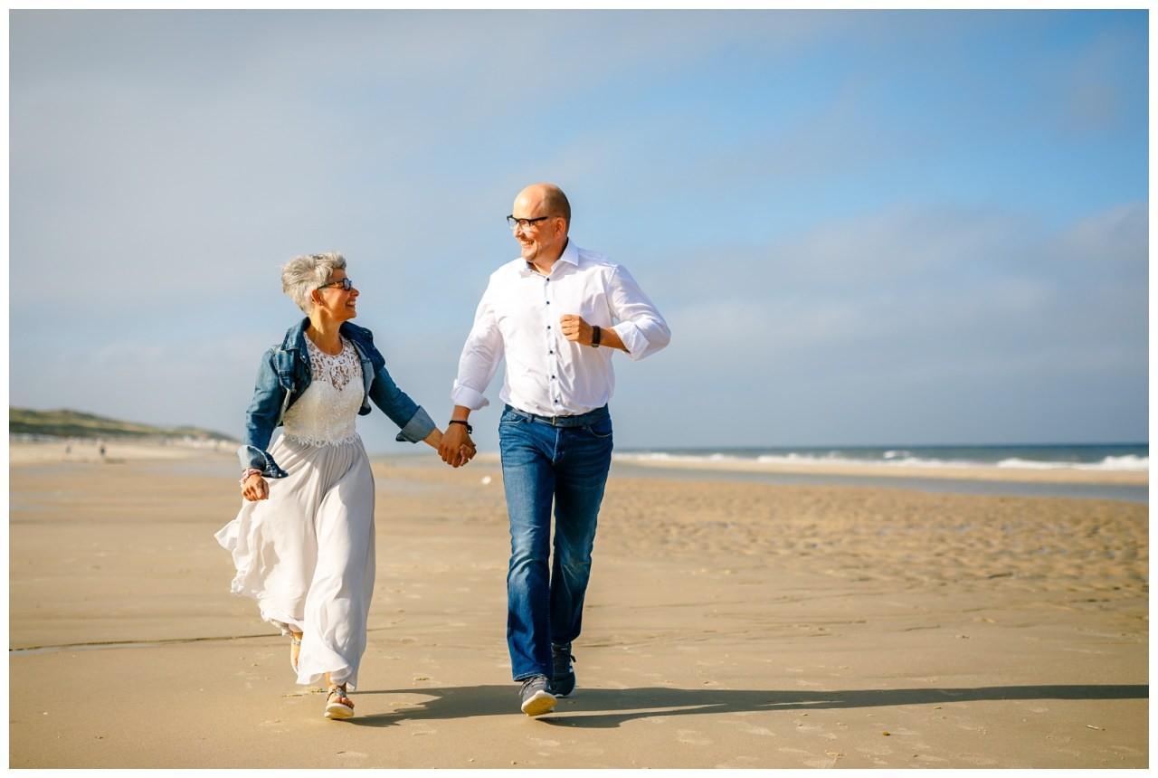Braut und Bräutigam rennen am Strand von Sylt.