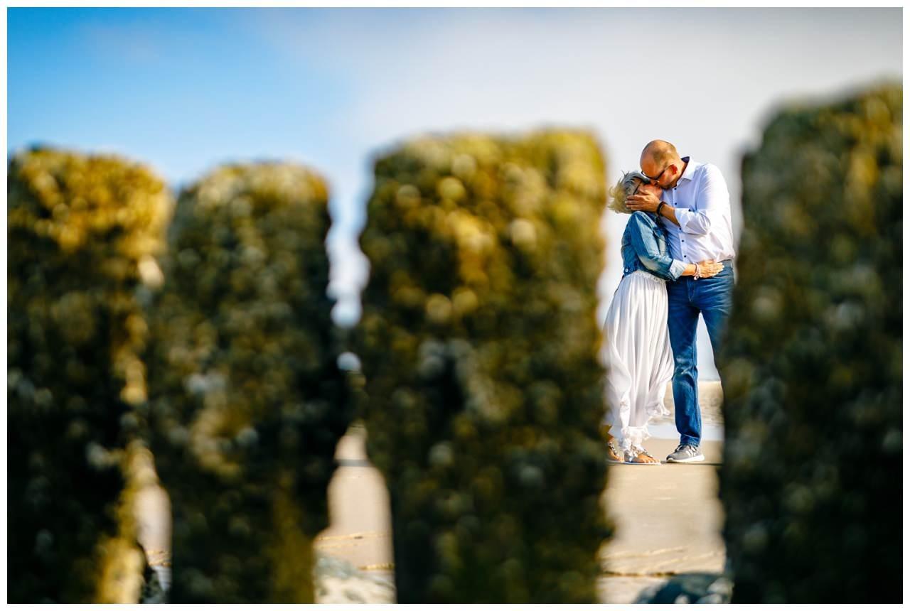Bei ihrer Hochzeit auf Sylt küssen sich Braut und Bräutigam am Strand.