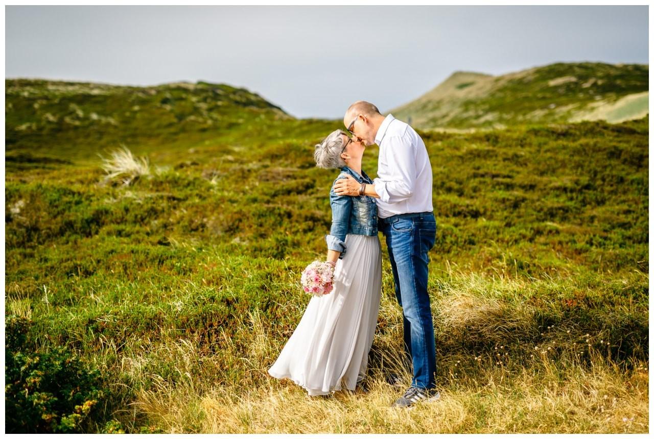 Brautpaar küsst sich in der Landschaft von Sylt.