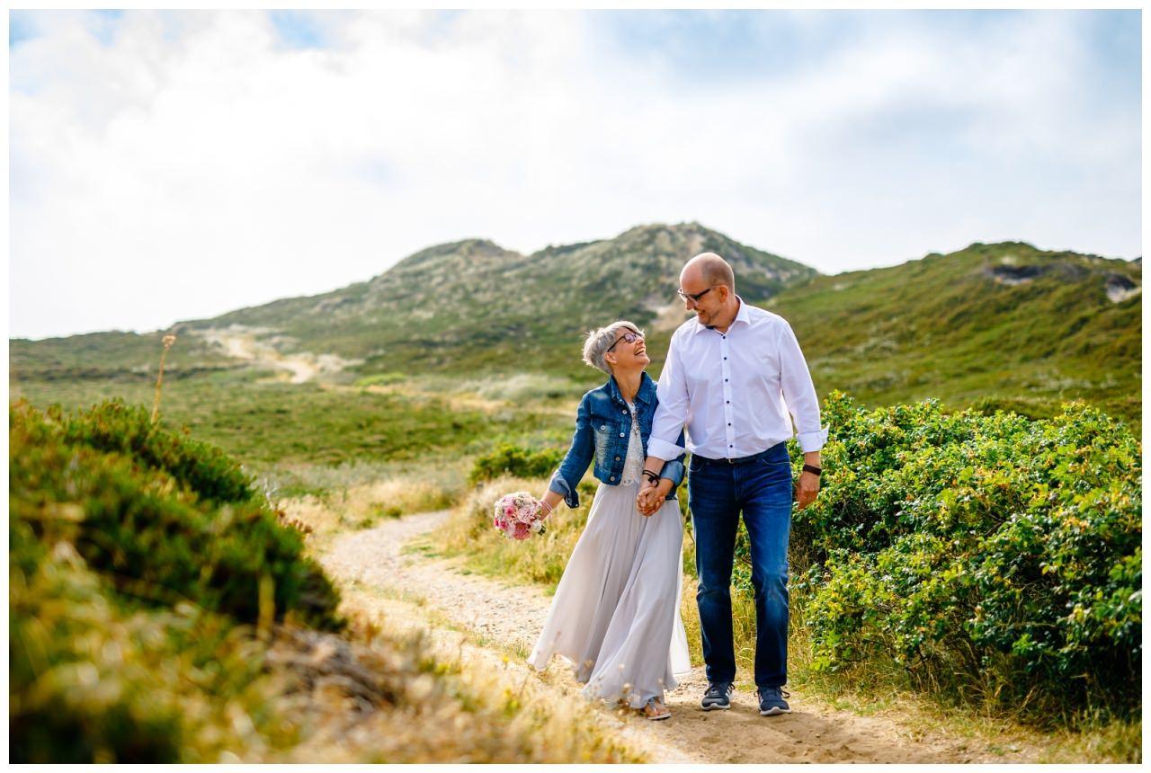 Die Braut und der Bräutigam gehen in den Dünen von Sylt spazieren.