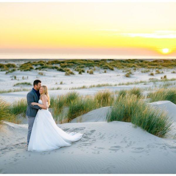 Hochzeitsshooting im Sonnenaufgang, das Brautpaar kuschelt am Strand.