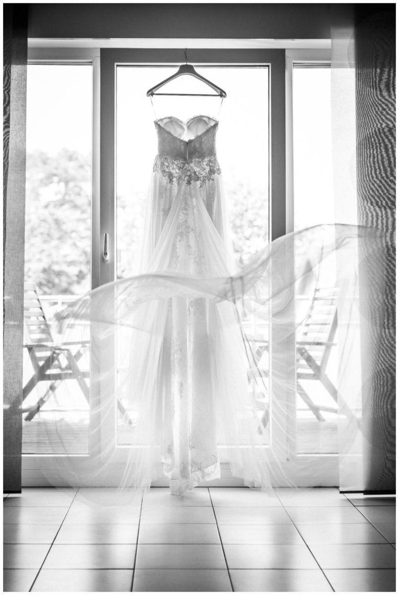 Das Brautkleid hängt vor der Hochzeit am Seepavillon Fühlinger See am Fenster.