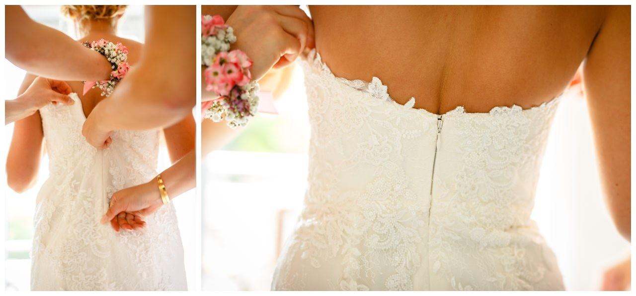 Brautkleid mit Spitze. Die Brautjungfern helfen der Braut beim Ankleiden.