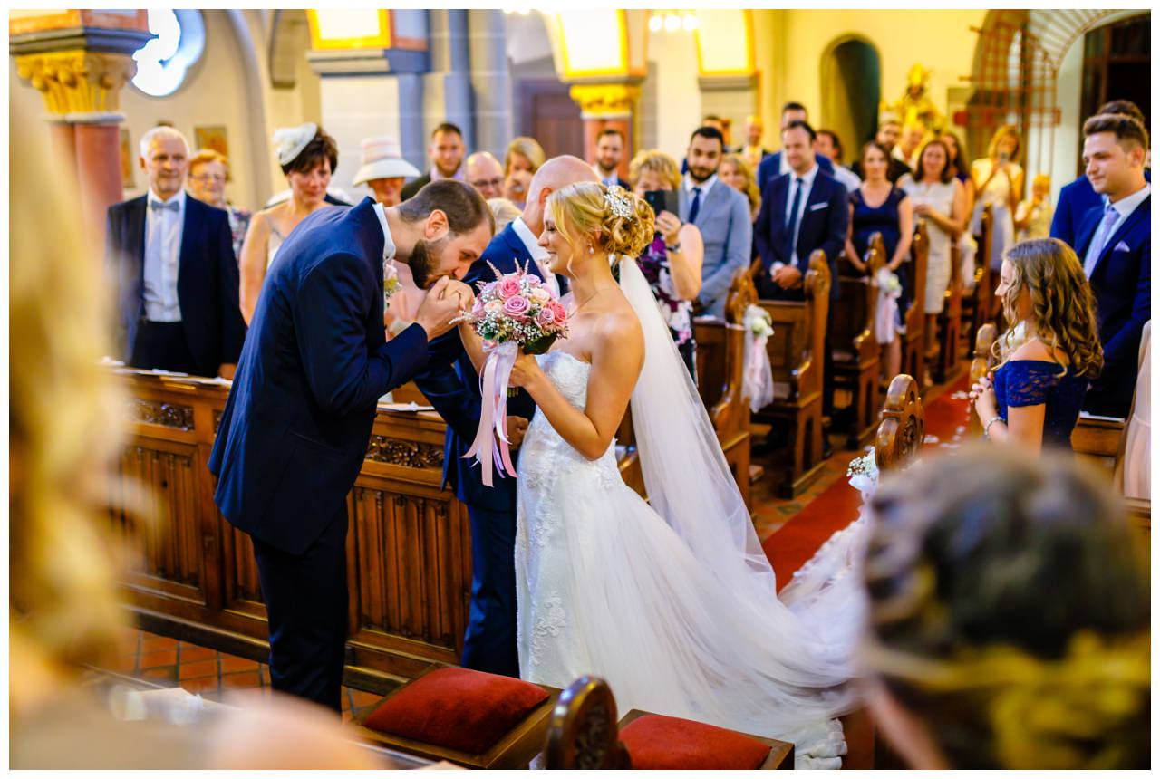 Der Bräutigam küsst die Hand der Braut beim Einzug in die Kirche.