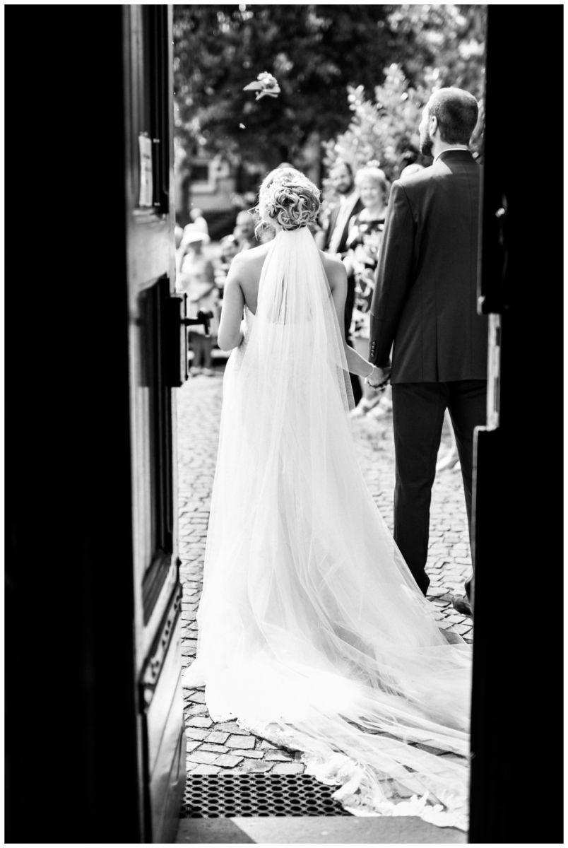 Braut und Bräutigam sind von hinten zu sehen wie sie aus der Kirche gehen.