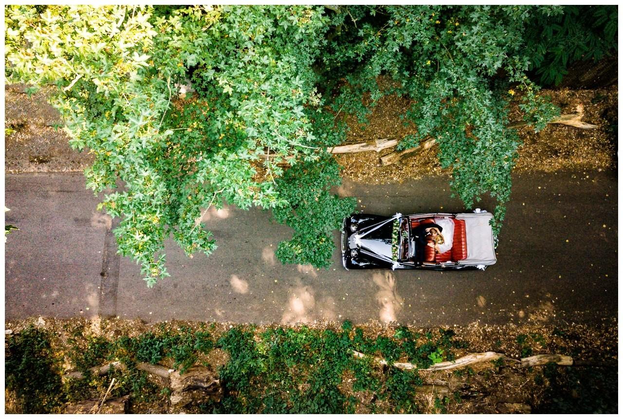 Drohnenfoto Braut und Bräutigam im Auto.