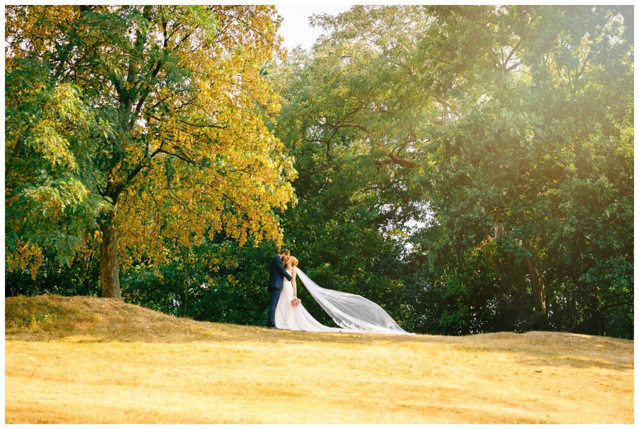 Hochzeitsfoto mit langem Schleier am Fühlinger See in Köln.