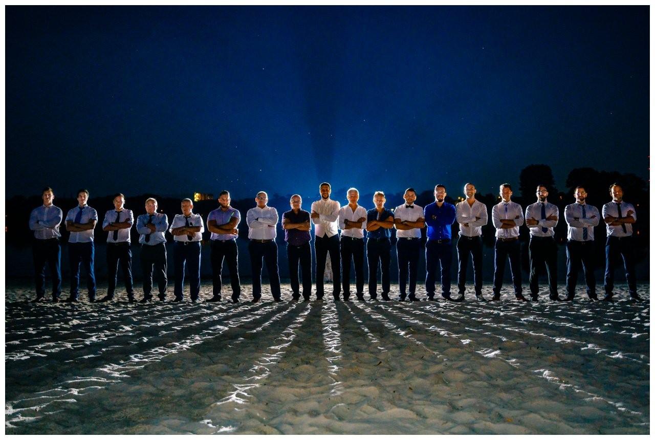 Gruppenfoto mit allen Männern auf der Hochzeit in Köln Fühling. Es ist dunkel.