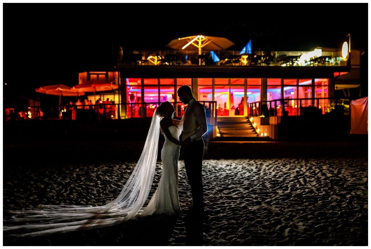 Hochzeit am Seepavillon Fühlinger See Das Brautpaar steht sich im dunkeln gegenüber. Im Hintergrund ist die beleuchtete Hochzeitslocation zu erkennen.