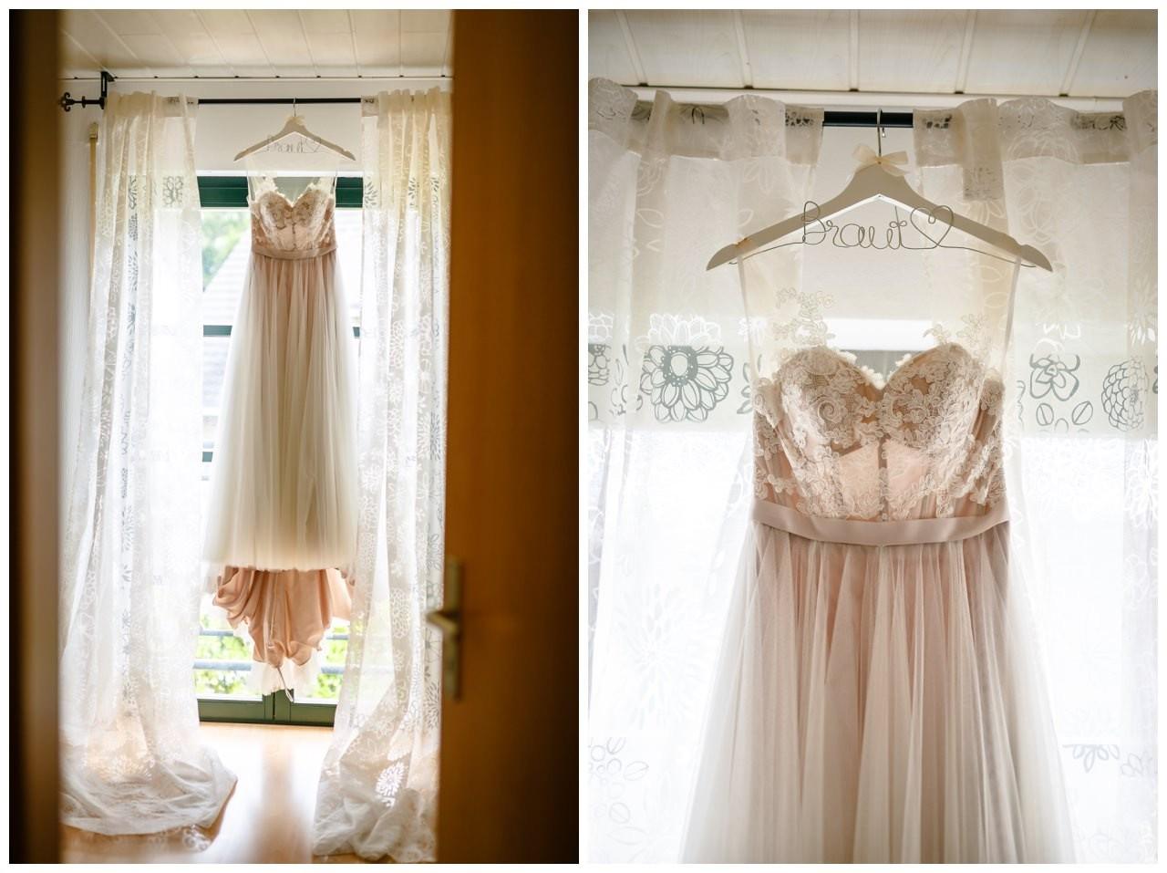 Das Brautkleid in blush hängt am Fenster vor der Hochzeit im Landgut am Hochwald in Sonsbeck.