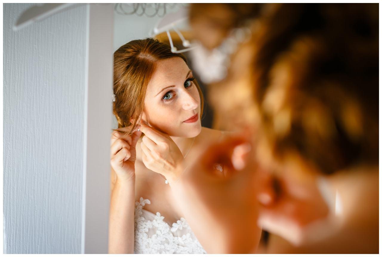 Die Braut steckt sich ihre Ohrringe an vor der Hochzeit im Landgut.