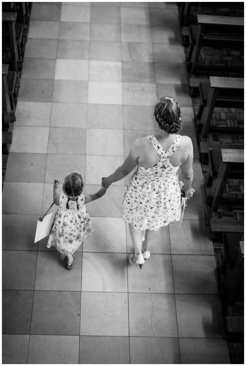 """Ein kleines Mädchen trägt das Schild """"Hier kommt die Braut""""."""