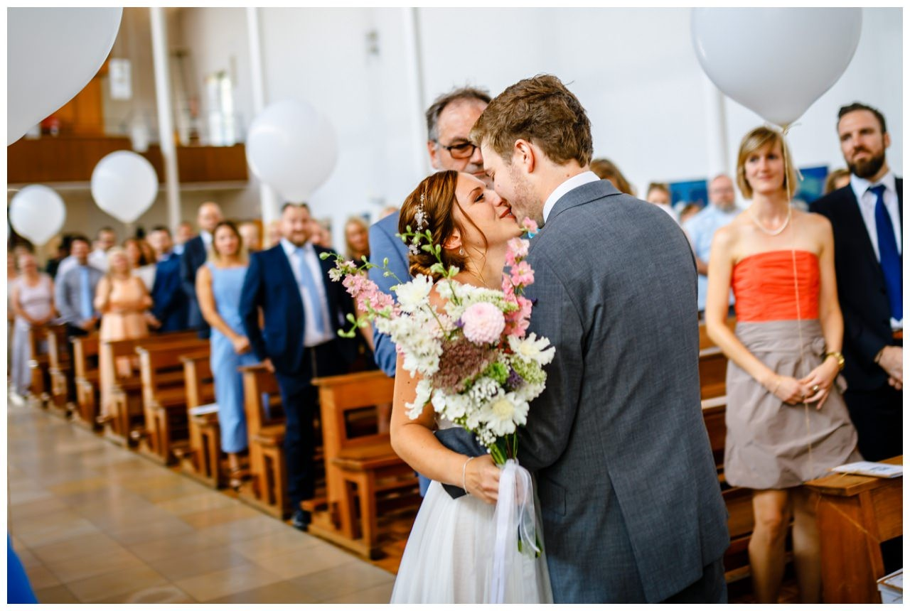 Der erste Kuss von Braut und Bräutigam bei der kirchlichen Hochzeit.