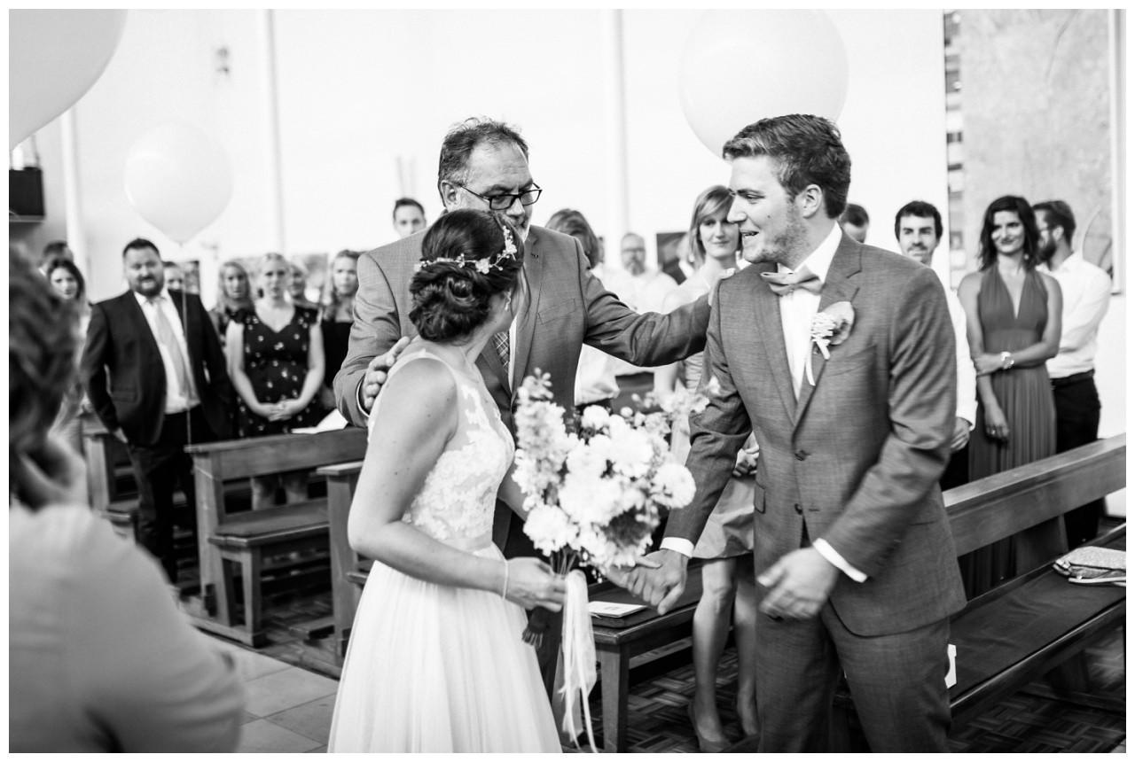 Der Vater der Braut überreicht die Braut in der Kirche an den Bräutigam.