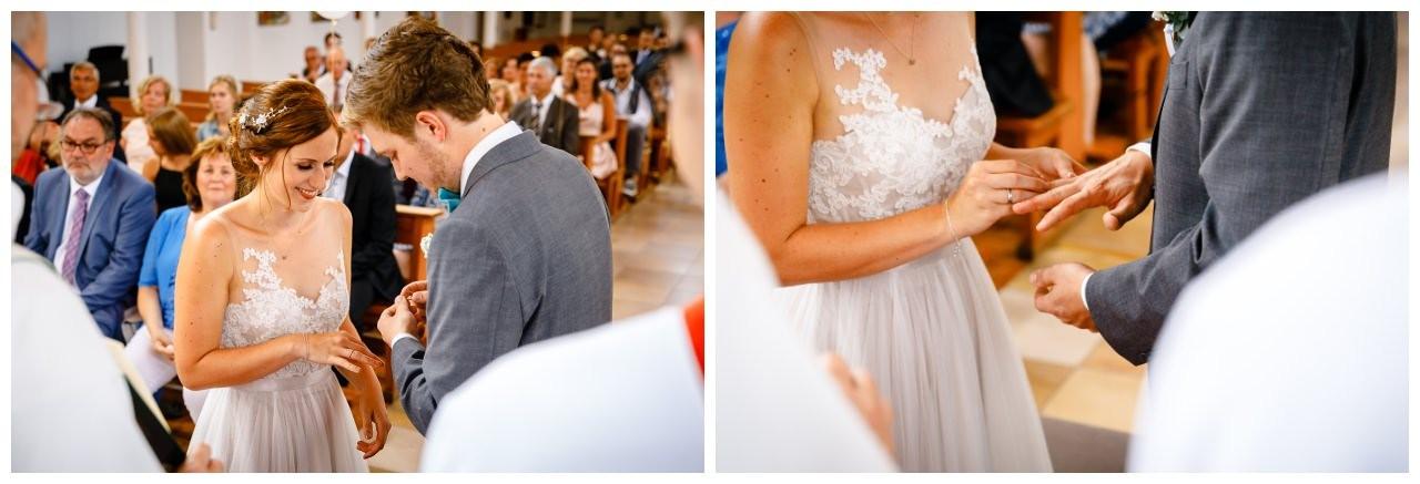 Das Brautpaar tauscht die Eheringe bei der kirchlichen Hochzeit am Niederrhein.