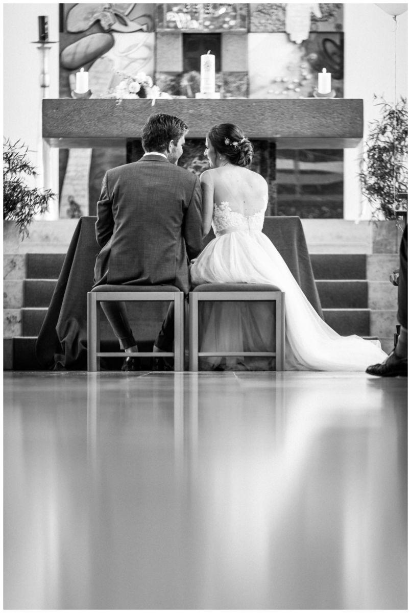 Das Brautpaar sitzt bei der kirchlichen Hochzeit vor dem Altar.