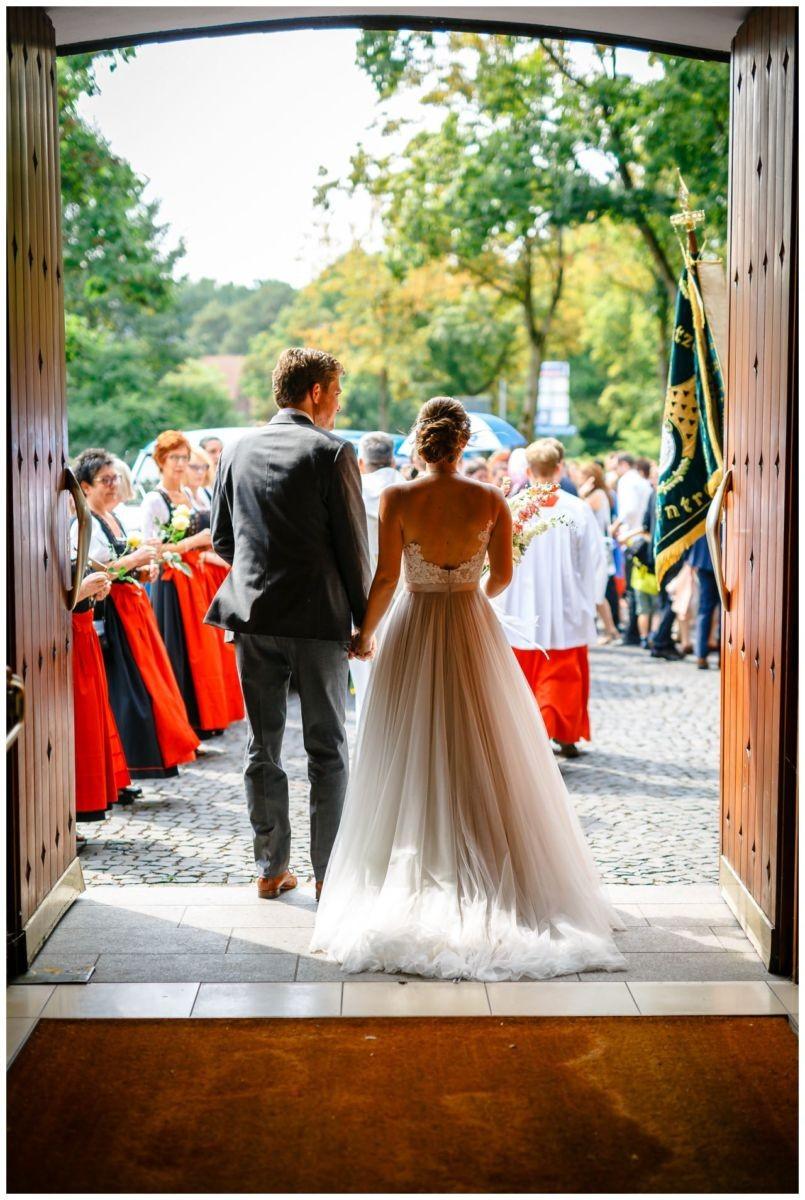 Das Brautpaar von Hinten beim Verlassen der Kirche.