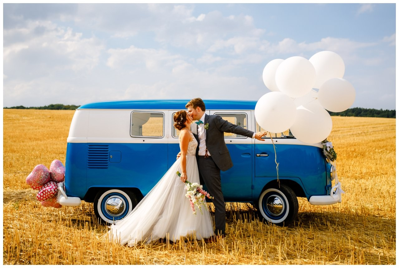 Hochzeitsfotos im Kornfeld mit einem alten VW Bulli bei der Hochzeit im Landgut am Hochwald.