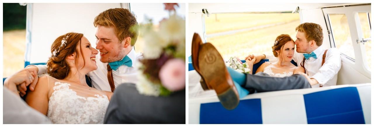 Braut und Bräutigam kuscheln in einem alten VW Bulli bei der Hochzeit in Sonsbeck.