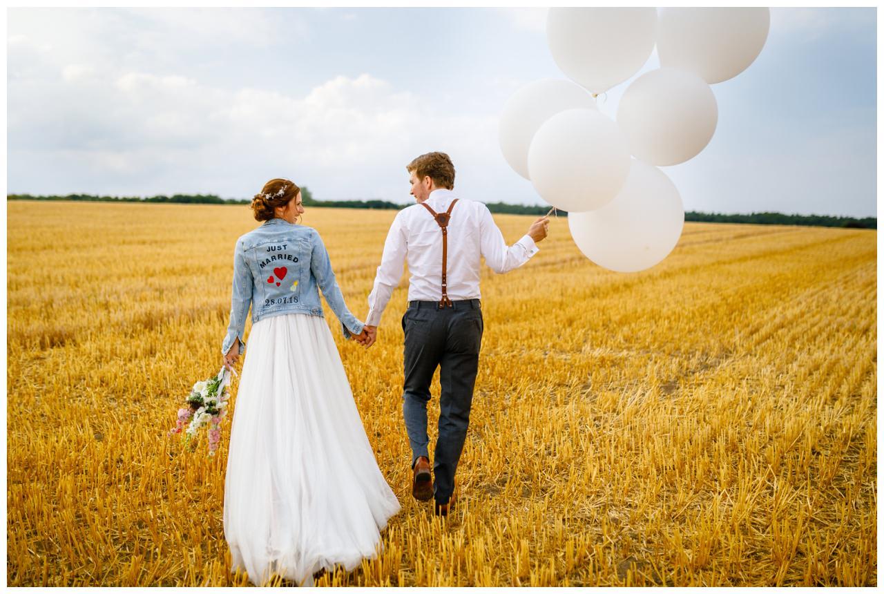 Braut udn Bräutigam spazieren mit Luftballons durch ein Kornfeld bei der Hochzeit im Landgut am Hochwald in Sonsbeck.
