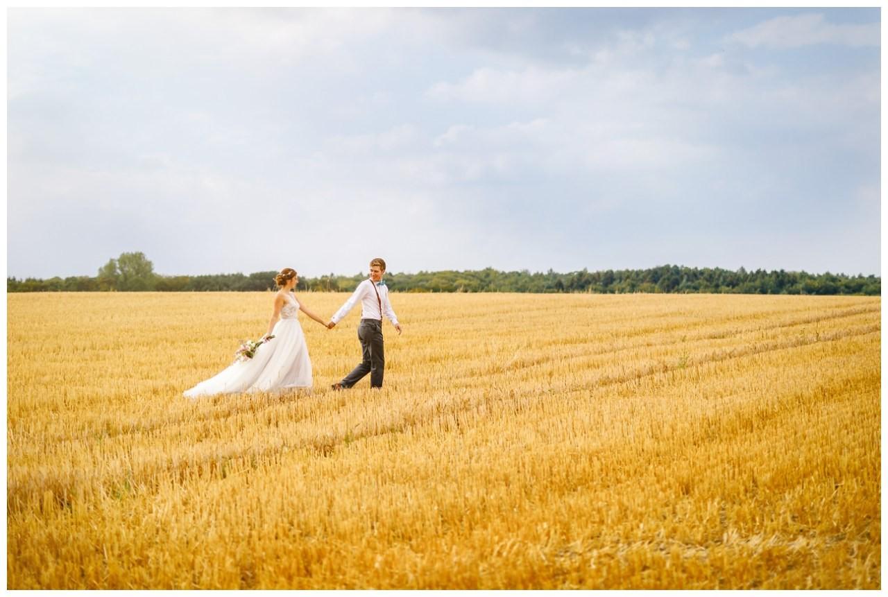 Das Brautpaar spaziert für die Hochzeitsfotos durch ein Kornfeld bei der Hochzeit im Landgut am Hochwald in Sonsbeck.