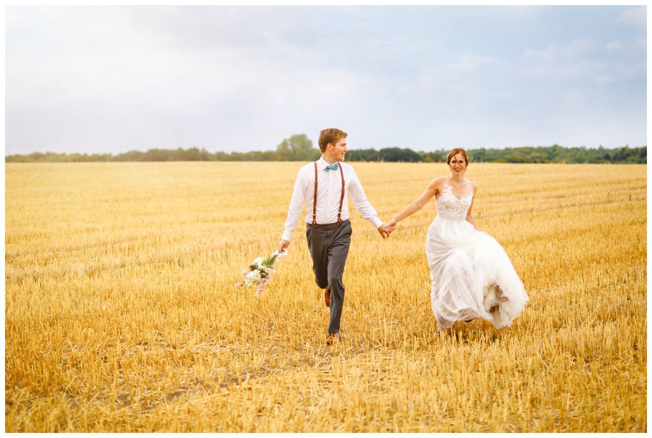Das Brautpaar rennt für die Hochzeitsfotos in Sonsbeck durch ein Kornfeld.