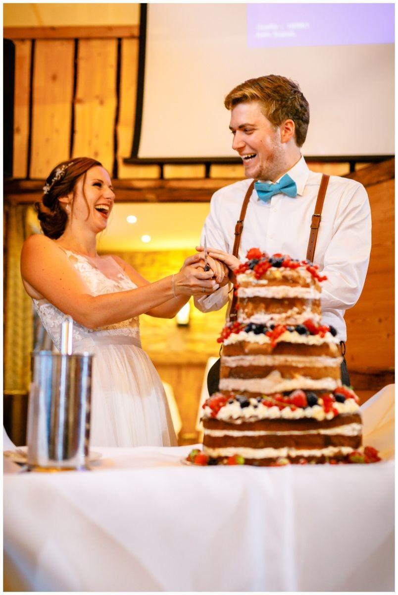 Das Brautpaar schneidet die Hochzeitstorte an. Es ist ein Naked Cake bei der Hochzeit im Landgut am Hochwald.