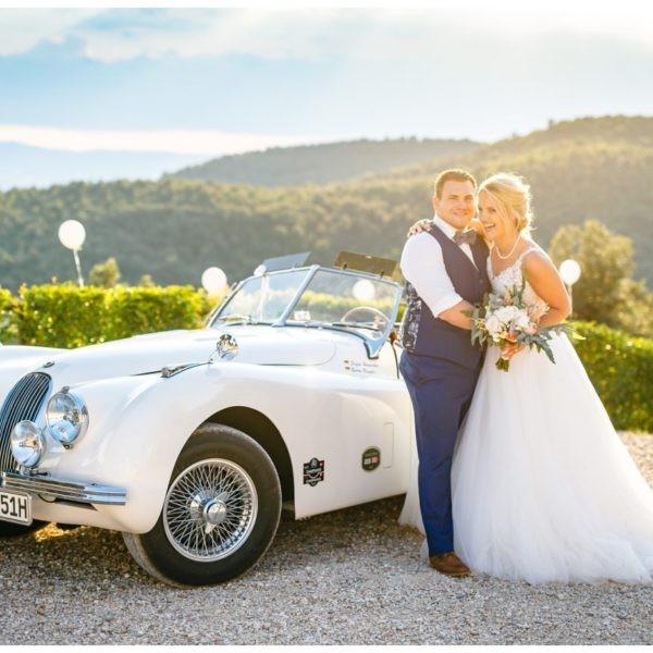 Hochzeitsfoto in Italien: Braut ud Bräutigam stehen vor der Brautauto und lachen.