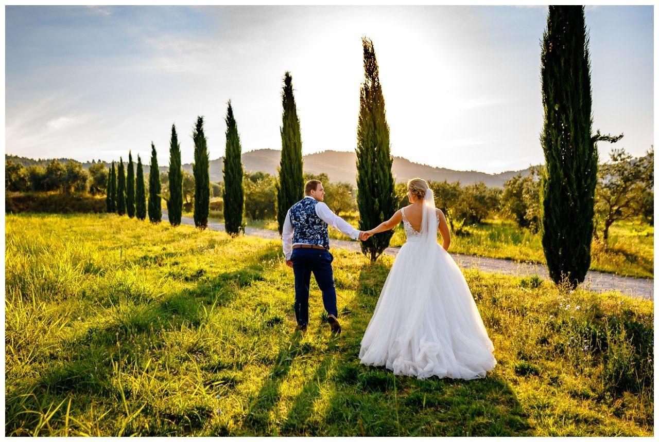 Bei dem After Wedding Shooting in der Toskana läuft das Brautpaar über eine Wiese, die umgeben ist von Zypressen.