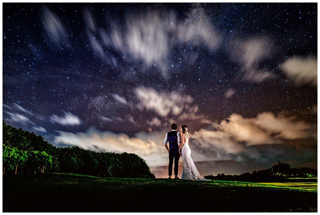 Hochzeit auf Mauritius, das Brautpaar steht bei der Nachtaufnahme unter dem Sternenhimmel.