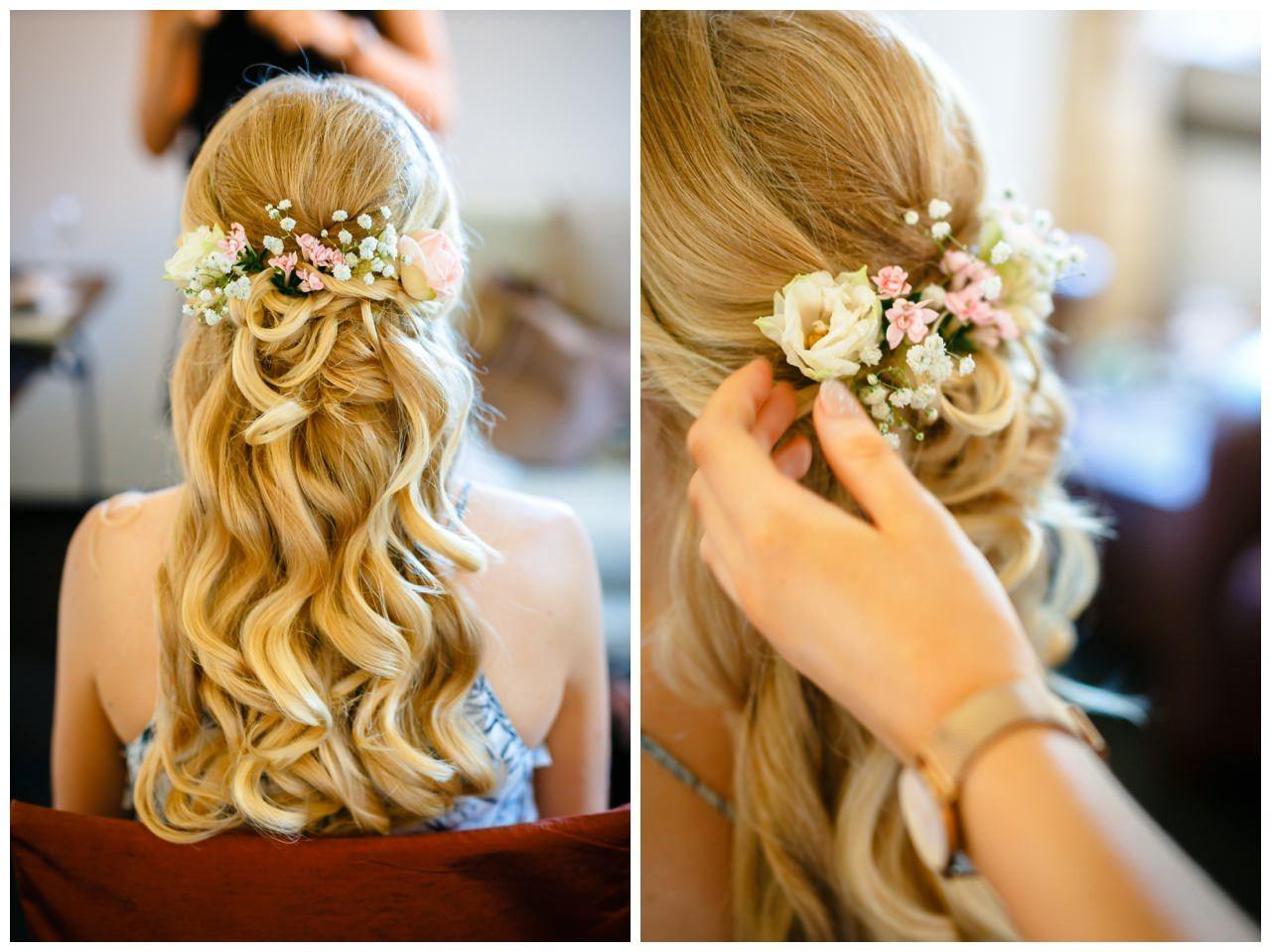 Brautfrisur halboffen mit frischen Blumen.