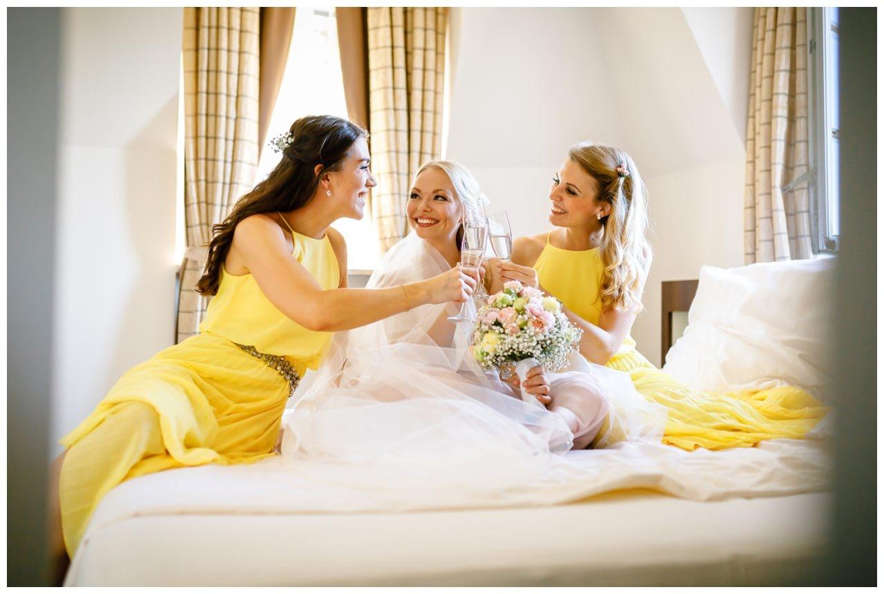 Bild mit den Brautjungfern vor der Hochzeit auf Schloss Berge. Die Mädels sitzen auf dem Bett im Hotel und stoßen mit Sekt an.