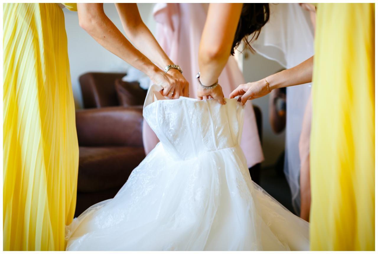 Die Brautjungfern halten das Kleid auf, damit die Braut hineinsteigen kann.