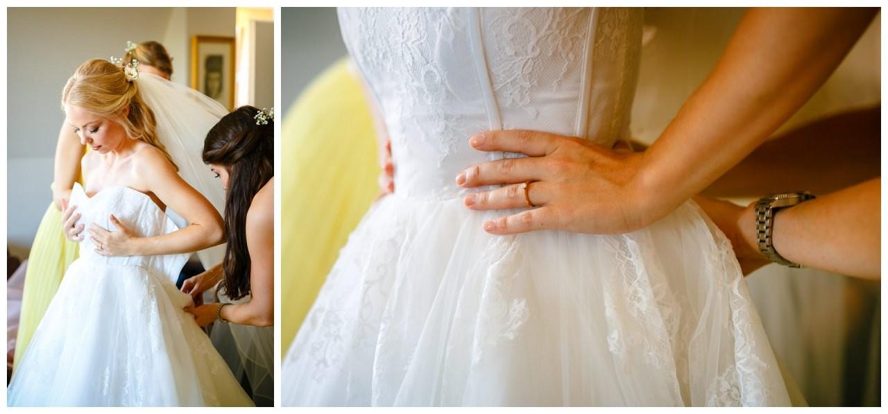 Die Braut zieht ihr Kleid an vor der Hochzeit auf Schloss Berge in Gelsenkirchen.