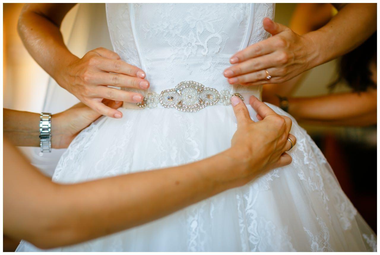 Die Brautjungfern helfen der Braut beim Anziehen. Man sieht nur die Hände um die Taille der Braut vor der Hochzeit auf Schloss Berge.