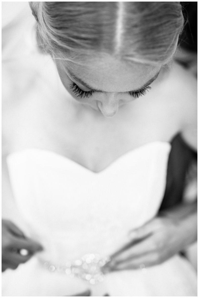 Die Braut zieht ihr Kleid an beim Getting Ready vor der Hochzeit auf Schloss Berge.